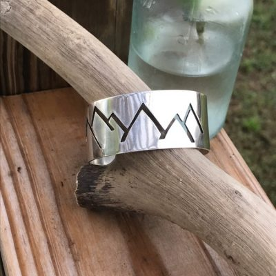 This hand sawed Mountain skyline is precisely pierced out of Sterling Silver and shaped for the Slope Lover.